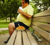 Overweight Man on Bench Eating Fast Food
