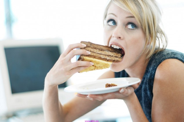 Close-up of a woman eating a large piece of cake