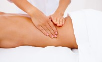 An attractive girl receiving back massage on white