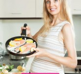 Happy cute pregnant woman cooking salmon at kitchen